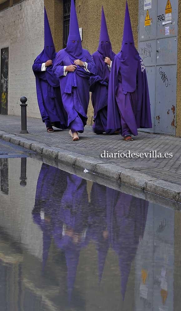Nazarenos de la Quinta Angustia regresan a casa en una tarde de Jueves Santo lluviosa. / Juan Carlos Vázquez
