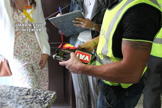 Un agente muestra los objetos intervenidos en el domicilio de los arrestados.