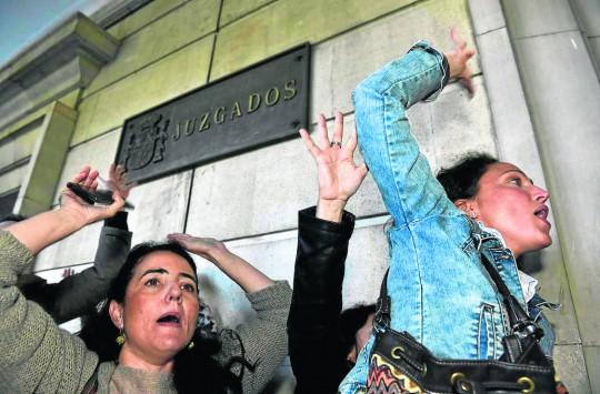 Un grupo de personas increpa a los ex presidentes a su llegada a los juzgados de Sevilla.