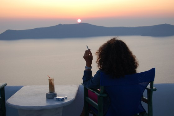 Penélope se entrega al placer con un cigarro y un frappé, frente al atardecer de Santorini. Esta es repetida, pero lo merece