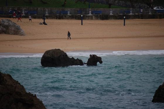 Paseantes por la invernal playa del Camello.