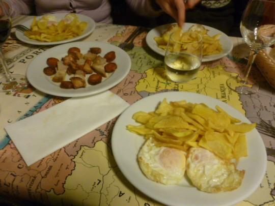 Huevos fritos con patatas para los tres, y torreznos, chorizo y lomo al centro.