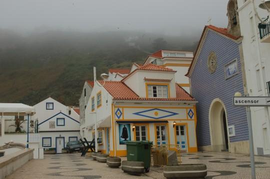 Casas tradicionales en en la playa de Nazaré. Arriba, entre la niebla, Sitio.