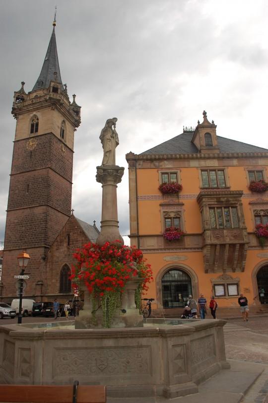 La Alcaldía, la fuente de Sainte Odile y la Torre en la Place du Marché.