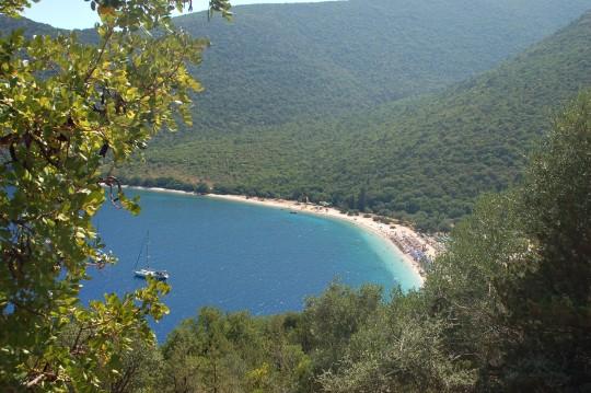 La playa de Antisamos, rodeada de verde, desde la carretera.