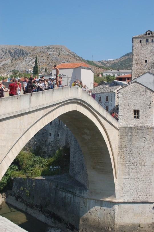 Desde el puente, saltadores a sueldo esperan que los turistas paguen por ver su salto.