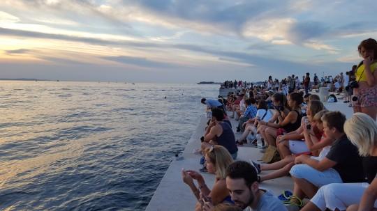Turistas al atardecer, sentados sobre el Órgano Marino de Zadar.