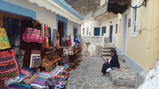Una mujer, ante sus labores a la venta en la calle principal de Olimpos.